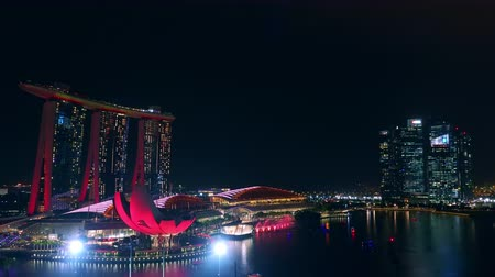 SINGAPORE - OCT 20, 2017: Fantastic night view of Marina Bay Sands Hotel and ArtScience museum illuminated by light show changing colors, reflections of city illumination in water. Fast motion video Стоковые видеозаписи