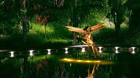 SINGAPORE - OCT 20, 2017: Magnificent Dragonfly Riders art sculptures at Dragonfly Lake in front of Gardens by the Bay. Tranquil water pond decorated with steel statues of flying insects at night.