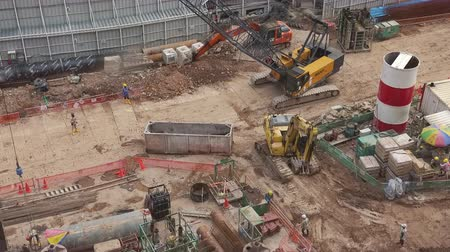 SINGAPORE - OCT 18, 2017: Excavators, cranes and hard hat workers working at urban construction site. Heavy equipment vehicles or machines moving and digging ground. Top view. Fast motion video. Stok Video
