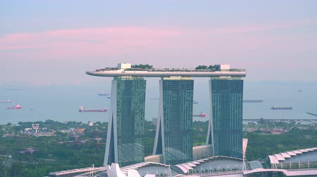 SINGAPORE - OCT 19, 2017: Amazing view of Marina Bay Sands hotel with swimming pool and restaurant on roof. Sunset zooming out panorama of beautiful resort in central district of modern Asian city Stok Video
