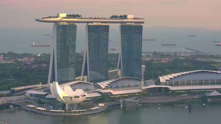 SINGAPORE - OCT 19, 2017: Amazing view of ArtScience or Lotus Flower Museum against Marina Bay Sands hotel at sunset. Skyscrapers illuminated by light of setting sun against colorful sky