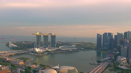 SINGAPORE - OCT 19, 2017: Amazing evening view of Marina Bay at sunset. Fantastic skyscrapers and buildings of modern architecture against setting sun and picturesque sky on background. Zooming out