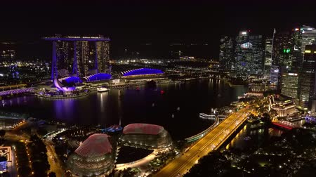 SINGAPORE - OCT 19, 2017: Fantastic night cityscape with buildings of Marina Bay Sands hotel, Esplanade Theatre on the Bay and Fullerton Hotel Futuristic view of cars moving on bridge over river