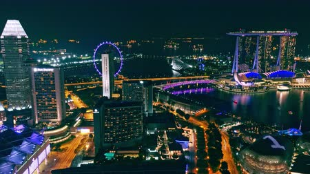 surpreendente : SINGAPORE - OCT 19, 2017: Fantastic night cityscape with buildings of Marina Bay Sands hotel, Esplanade Theatre on the Bay and Singapore Flyer wheel illuminated by colorful lights. Futuristic view