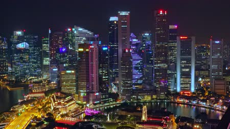 SINGAPORE - OCT 19, 2017: Fantastic night view of Singapore city center with beautiful historical buildings illuminated by colorful lights against river and Marina Bay Financial Centre on background.