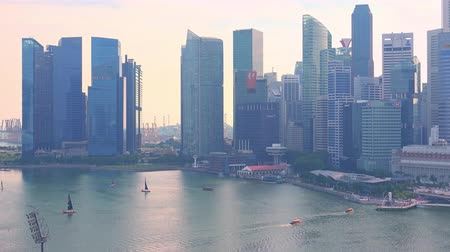 SINGAPORE - OCT 20, 2017: Cityscape at  Marina Bay Financial Center against sunset sky on background. Yachts sailing in front of fantastic modern skyscrapers and buildings at Asian city Stok Video