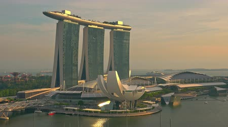 SINGAPORE - OCT 20, 2017: Amazing view of ArtScience or Lotus Flower Museum against Marina Bay Sands hotel at sunset. Skyscrapers illuminated by light of setting sun against colorful sky
