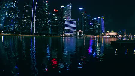 SINGAPORE - OCT 20, 2017: Fantastic night view of Asian city with tall futuristic buildings and skyscrapers with window lights reflecting in rippling water. Beautiful cityscape modern megalopolis