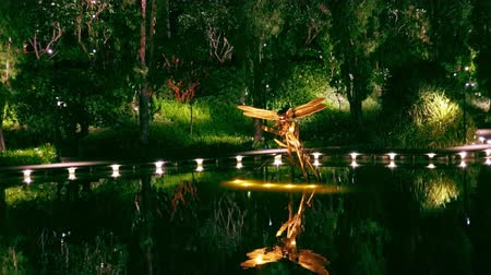 SINGAPORE - OCT 20, 2017: Magnificent Dragonfly Riders art sculptures at Dragonfly Lake in front of Gardens by the Bay. Tranquil water pond decorated with statues of flying insects at night. Zoom out
