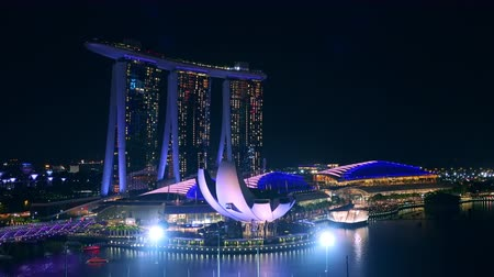 SINGAPORE - OCT 20, 2017: Fantastic night view of  illuminated Marina Bay Sands Hotel and ArtScience museum, cruise boat passing by. Amazing view of central area or downtown core of modern Asian city