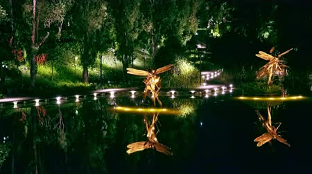 libélula : SINGAPORE - OCT 20, 2017: Magnificent Dragonfly Riders art sculptures at Dragonfly Lake in front of Gardens by the Bay. Tranquil water pond decorated with steel statues of flying insects at night.