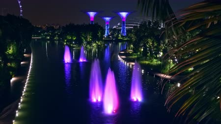 SINGAPORE - OCT 21, 2017: Magnificent fountains at Dragonfly Lake in front of Gardens by the Bay against Supertree Grove with tall artificial trees on background.