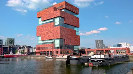 belga : ANTWERP, BELGIUM - MAY 26, 2018: Amazing view of facade of MAS Museum aan de Stroom located along Scheldt river. Building of unusual postmodern architecture and boats or yachts moored at riverbank.