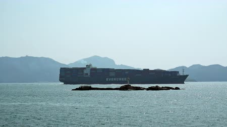 HONG KONG - OCT 27, 2017: Freighter ship, barge or boat carrying containers to sea or ocean port. Marine vessel with freight on board goes to seaport or cargo terminal. Maritime transportation.