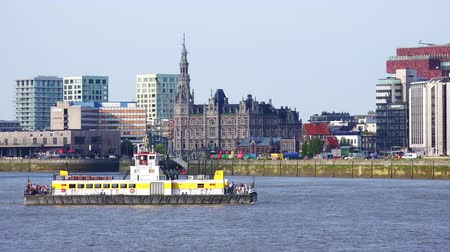 belga : ANTWERP, BELGIUM - MAY 26, 2018: Gorgeous panoramic cityscape with touristic ship, vessel or pleasure boat sailing along Scheldt river against Pilotage building and Museum aan de Stroom on background.