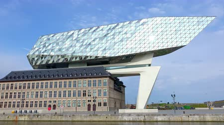 ANTWERP, BELGIUM - MAY 27, 2018: Sun reflecting in shiny glass facade of Antwerp Port Authority building designed by Zaha Hadid. Fantastic view of modern city landmark on sunny day.