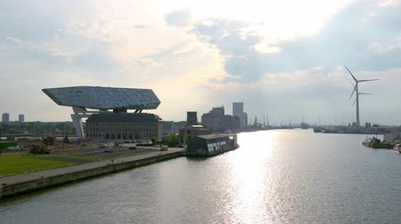 ANTWERP, BELGIUM - MAY 27, 2018: Sunset view of rotating wind turbines and Antwerp Port House. Futuristic postmodern architecture created by Zaha Hadid. Impressive building of seaport authority.