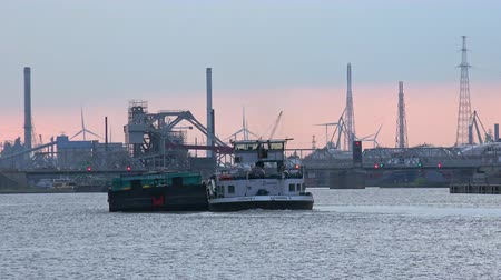 ANTWERP, BELGIUM - MAY 27, 2018: Loaded barge passing by Antwerp international seaport at  Scheldt river. Silhouettes of cranes, drawbridge and rotating wind turbines view against sunset sky. Stok Video