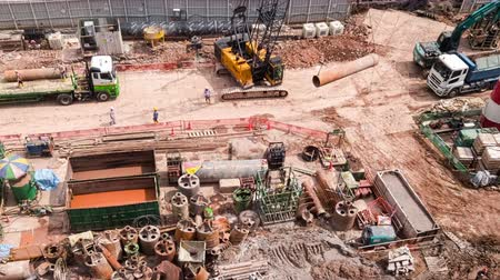 SINGAPORE - OCT 19, 2017: Top panoramic or aerial view of urban construction site with cranes unloading trucks and hard hat workers. Work of heavy equipment vehicles or machines. Time lapse Stok Video