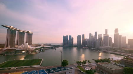 Amazing view of Marina Bay at sunset. Fantastic skyscrapers and buildings of modern architecture against picturesque sky on background. Setting sun reflecting in office windows and water. Time lapse