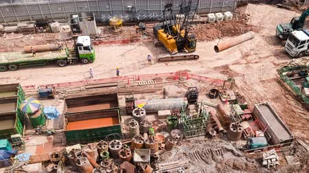 SINGAPORE - OCT 19, 2017: Top or aerial view of urban construction site with cranes unloading trucks and hard hat workers. Work of heavy equipment vehicles or machines. Time lapse