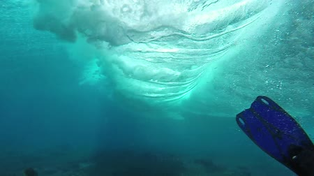 alatt : Surfing wave breaking over coral reef passes snorkeler, slow motion underwater view