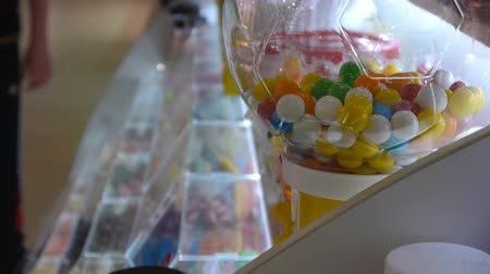 doces : Gumball Machine And Other Candy In The Shopping Center And Peoples On Blurred Background. Children Hands Choose Candy