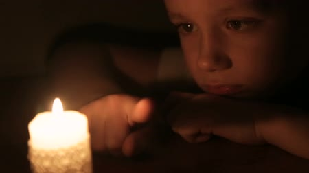família : The boy touches the wax of a burning candle