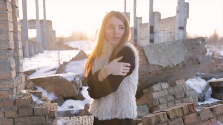 it's cool : Girl in a sheepskin coat on a background of an abandoned building.slow motion