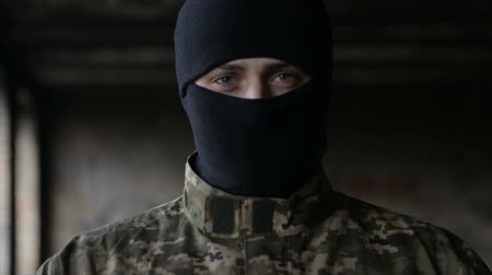 wall building feature : A man in camouflage and a black mask on an old abandoned building Stock Footage