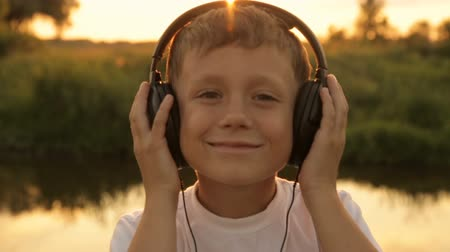 zahmetsiz : Boy listening to music through headphones in the nature under the sunset Stok Video