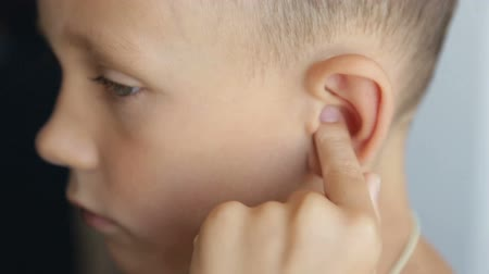 earlobe : The boys finger massages the left ear Stock Footage