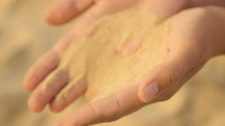 clasped : Sea sand is poured from womens hands Stock Footage