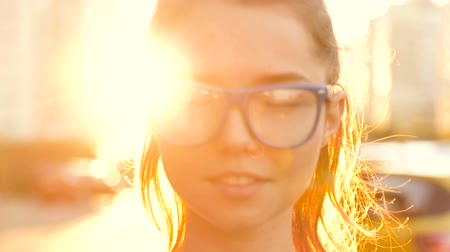 lightweight : Girl in glasses on the background of sunset