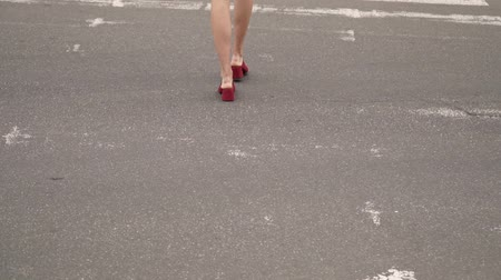 but : A girl in red shoes crosses the road. A womans gait.