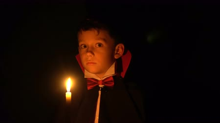 vampiro : Boy in vampire costume posing for camera, makeup as evil spirits on Halloween Stock Footage