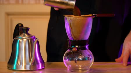 yalıtımlı : Barista makes coffee, pours hot water through a filter into a glass flask Stok Video