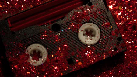vcr : Black video cassette on the background of red glitter Stock Footage
