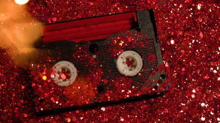 軽量 : Black video cassette on the background of red glitter 動画素材