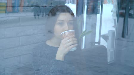 A girl in a cafe drinks hot chocolate from a paper cup Stock mozgókép