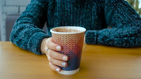A paper cup with a warm cappuccino in the hands of a girl.