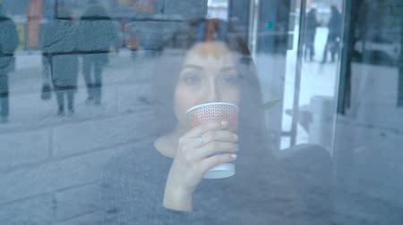 A girl in a cafe drinks hot chocolate from a paper cup Стоковые видеозаписи