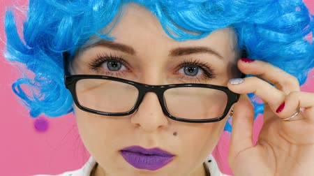 peruka : Portrait of a girl in a blue wig and glasses on a crimson background Wideo