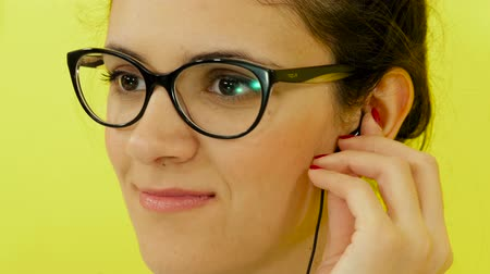 Portrait of a girl on a yellow background in headphones and glasses Стоковые видеозаписи