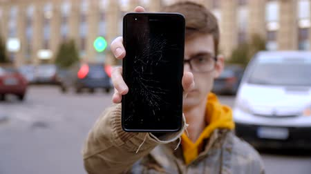 The concept of a broken gadget. Frustrated young man shows a smartphone with a broken screen. Стоковые видеозаписи