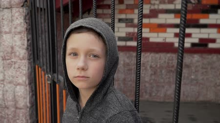 Portrait of a boy near the metal fence Stock mozgókép