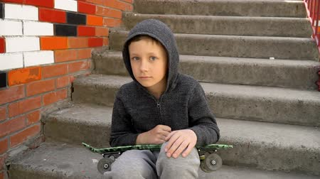 The boy sits on the steps and holds a skateboard in his hands Стоковые видеозаписи