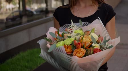 Girl holding a bouquet of fresh flowers in her hands Стоковые видеозаписи