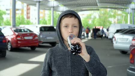 The boy is drinking from a plastic bottle, slow motion