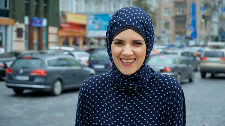 cami : Muslim woman laughs on the background of cars Stok Video